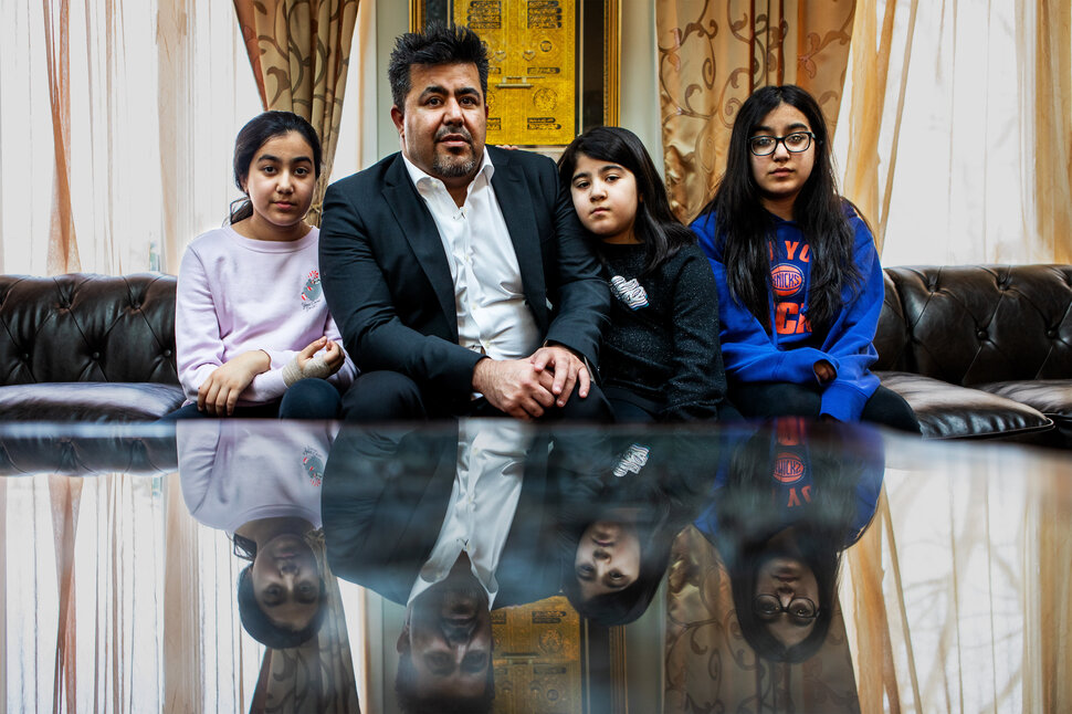 Omarkheil and his daughters in their home.He is worried he might have to sell his home if he doesn't find work so
