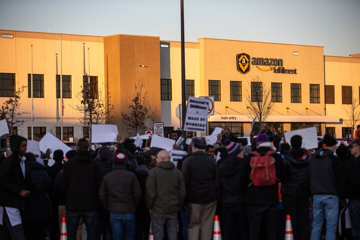 Demonstrators shout slogans and hold placards during a protest at the Amazon fulfillment center in Shakopee, Minnesota, Dec.