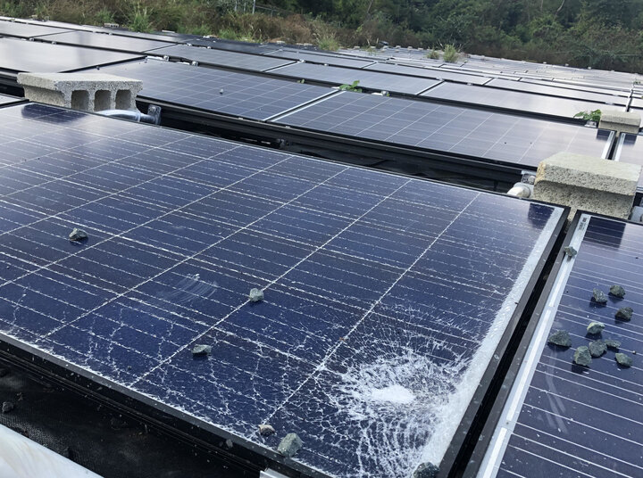 A shattered Tesla solar panel outside a water facility.