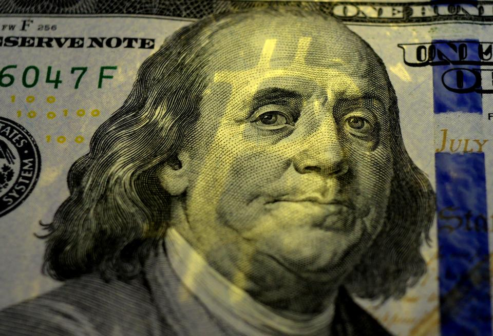 The shadow of Bitcoin on Benjamin Franklin's face on the one hundred dollars USA. Money concept.