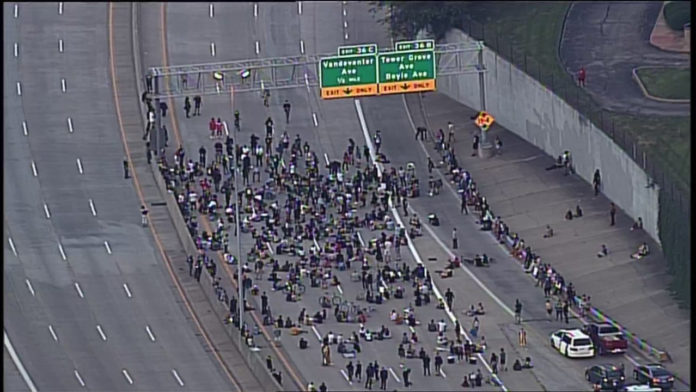 Protesters march onto I-64 near Vandeventer
